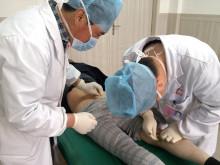 图为小针刀医师在进行腿部治疗