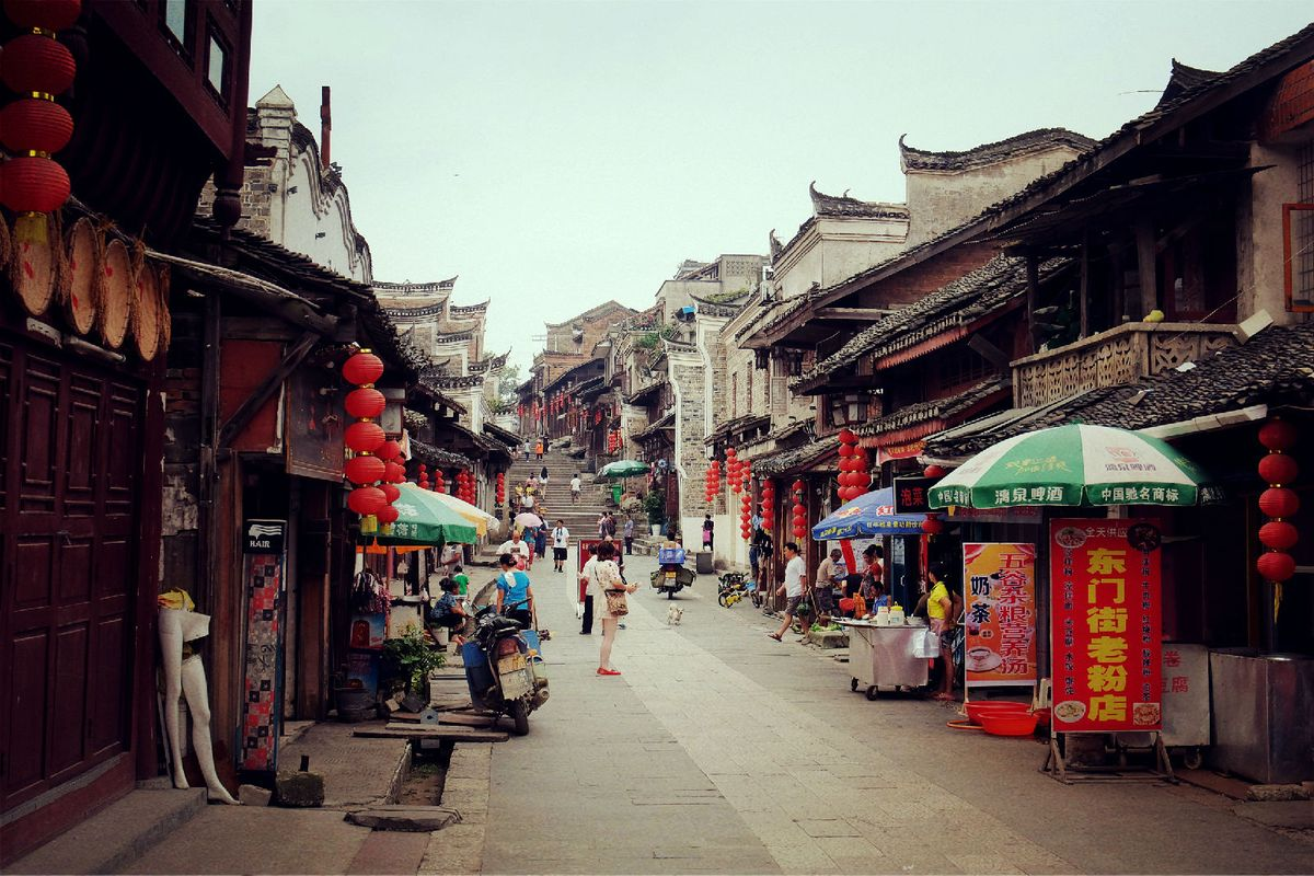 街两边是明清建筑风格的铺面房屋,白墙灰瓦,飞檐高脊,墙上彩绘图案图片