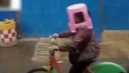 """大妈骑车未带雨具 板凳套头当""""雨伞"""""""